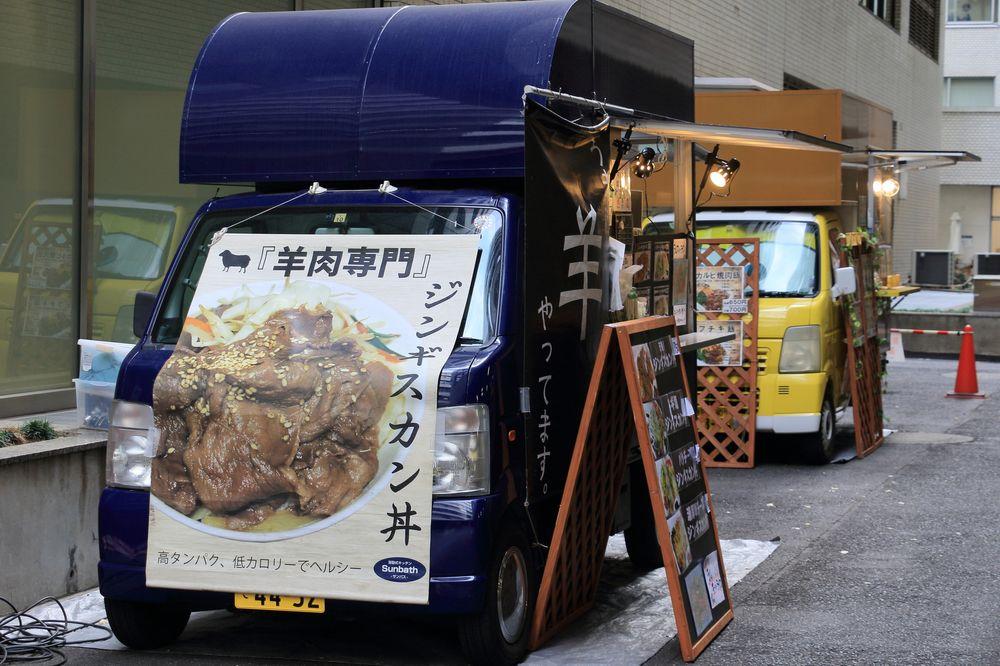 ジンギスカン丼の広告を付けた紺色のキッチンカー