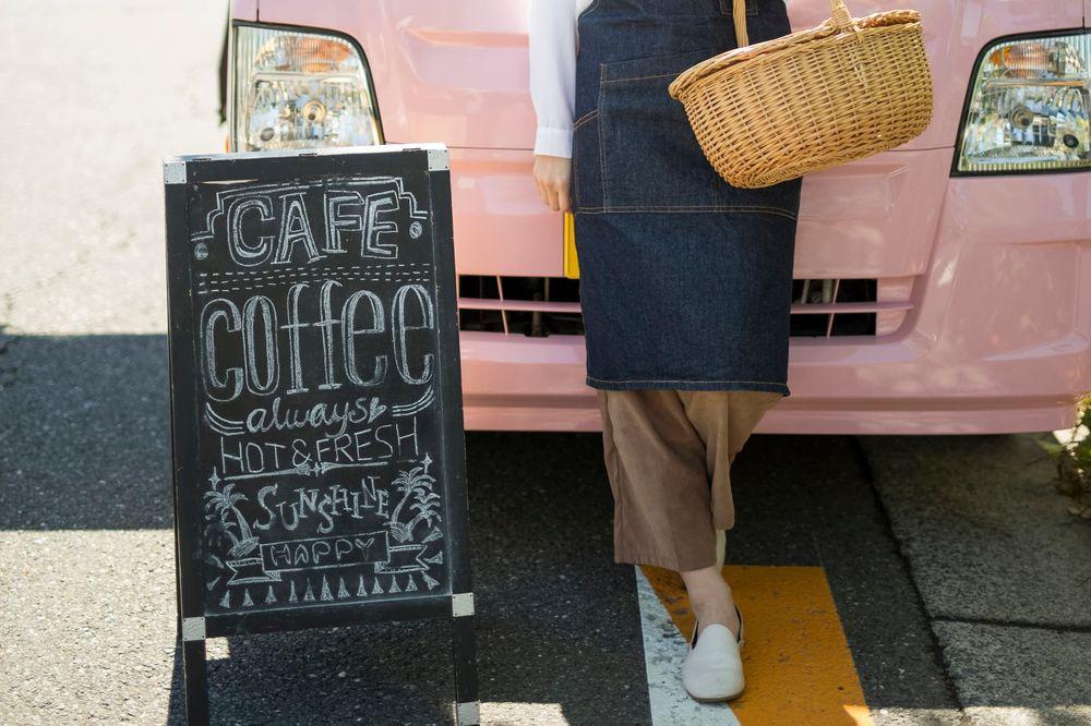コーヒーカフェの看板とピンク色のキッチンカー